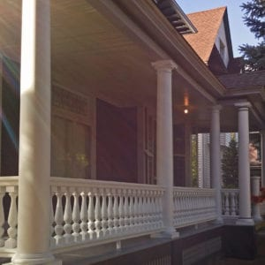 Front porch railing with Revival spindles and round tapered columns